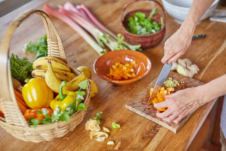 trinchante: Mature woman chopping vegetables, focus on hands