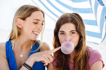 gumballs: Portrait of two young female friends popping bubblegum bubble on beach