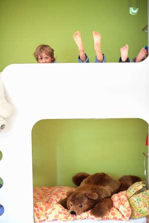literas: Tres muchachos en la litera superior de litera, espiando hacia fuera, descalzo