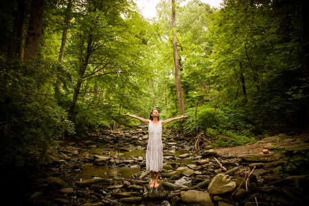 secluded: Mid adult woman standing barefoot on rocky riverbed wearing white dress, arms raised open looking up