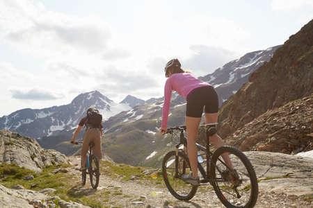 Rear view of young couple mountainbiking at Val Senales Glacier, Val Senales, South Tyrol, Italy