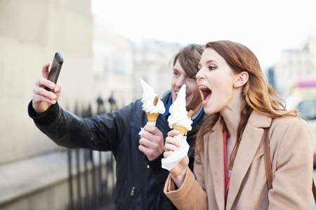 Couple with ice cream cones taking smartphone selfie, London, UK