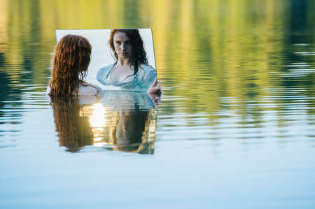 Young woman standing in lake, holding mirror, looking at reflection