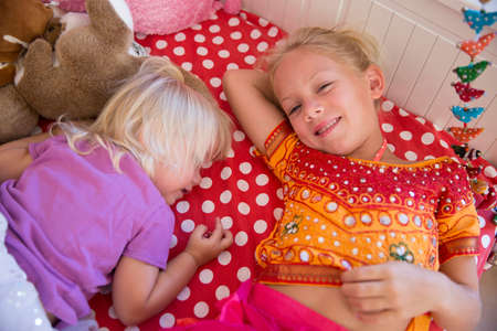 Portrait of two young sisters lying on bed