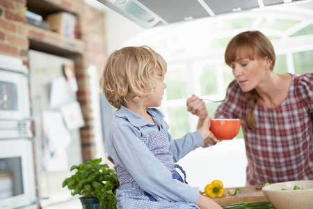 Mother and son preparing meal in kitchen LANG_EVOIMAGES