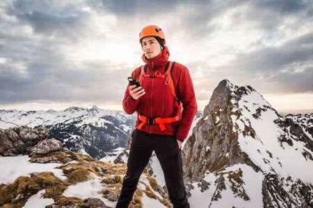 Hiker holding gps, Kellenspitze, Tannheim mountains, Tyrol, Austria LANG_EVOIMAGES