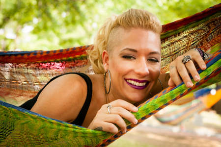 Portrait of mid adult woman with shaved blond hair lying in garden hammock