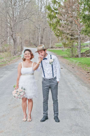 Portrait of bride and groom on country road, holding hands, smiling LANG_EVOIMAGES