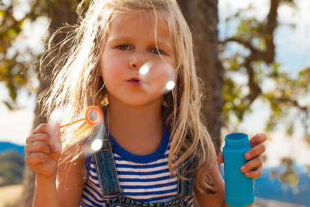 getting out: Girl blowing bubbles in park