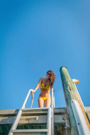 getting out: Low angle view of young woman on sea pier