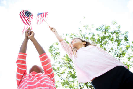 Girls holding up American flags in park LANG_EVOIMAGES