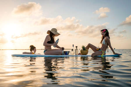 Two young women preparing cocktails on paddleboard at sunset, Islamorada, Florida, USA