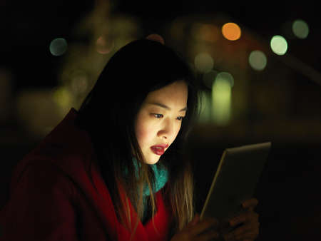Young woman outdoors at night, face illuminated by digital tablet LANG_EVOIMAGES