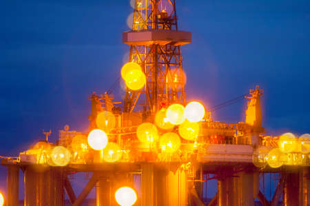Vista borrosa de la plataforma de perforación iluminada en la noche LANG_EVOIMAGES