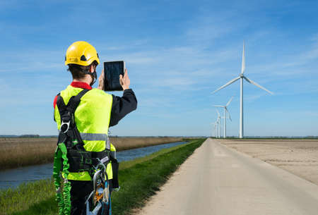 environmental issues: Maintenance worker taking photography of wind farm using digital tablet, Biddinghuizen, Flevoland, Netherlands LANG_EVOIMAGES