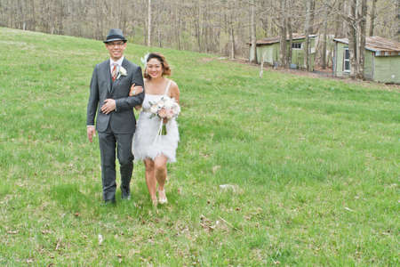 30 years old married couple: Bride and groom walking across field, arm in arm, smiling