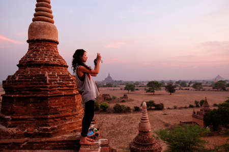 sunrises: Woman taking photograph of view, Bagan Archaeological Zone, Buddhist temples, Mandalay, Myanmar LANG_EVOIMAGES
