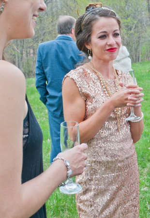 ceremonial make up: Mid adult woman holding drink and speaking with friends at wedding LANG_EVOIMAGES