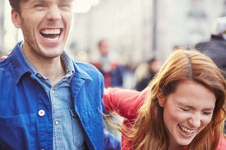 Couple laughing on street, London, UK