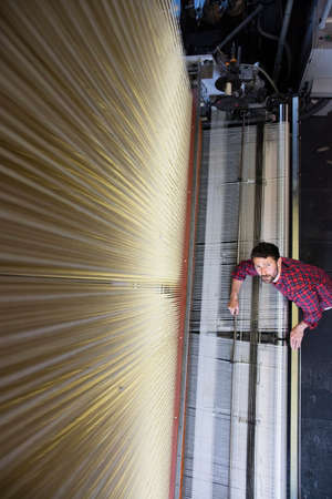 weavers: Overhead portrait of young male weaver and old weaving machine in textile mill