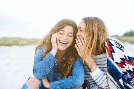 Two young female friends whispering on beach