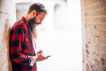 Side view of man with beard holding smartphone LANG_EVOIMAGES