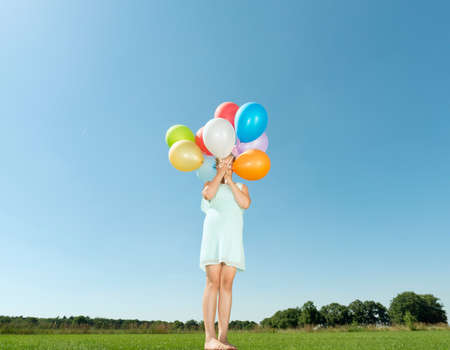 Girl holding bunch of balloons in front of her face in field LANG_EVOIMAGES