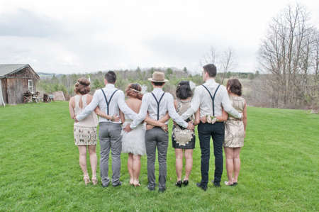 receptions: Bride and groom with friends, arms around each other, rear view LANG_EVOIMAGES