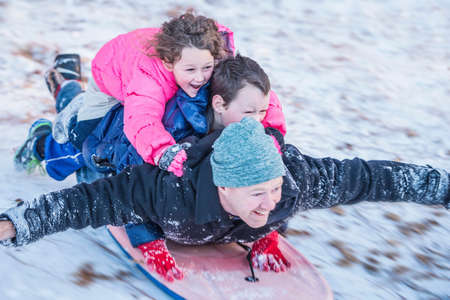 Portrait of father, son and daughter laying on top of each other riding sledge down hill