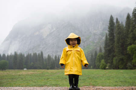 Portrait of female toddler wearing yellow raincoat in front of misty mountain, Yosemite National Park, California, USA