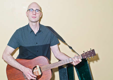Portrait of bald mid adult man wearing spectacles playing acoustic guitar LANG_EVOIMAGES
