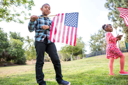 Children playing with American flag in park