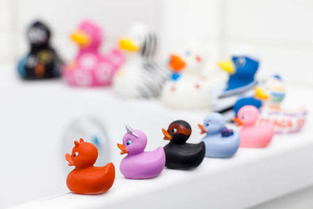 Various rubber ducks sitting on edge of bath