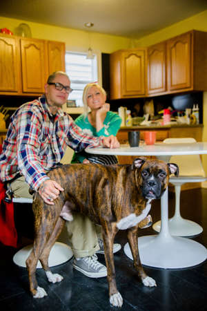 pooches: Couple sitting at dining table with boxer dog