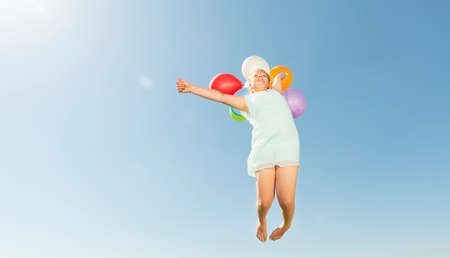 athletic wear: Girl holding bunch of balloons jumping mid air against blue sky LANG_EVOIMAGES