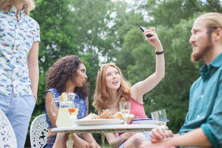 puckered lips: Friends taking selfie and enjoying garden party