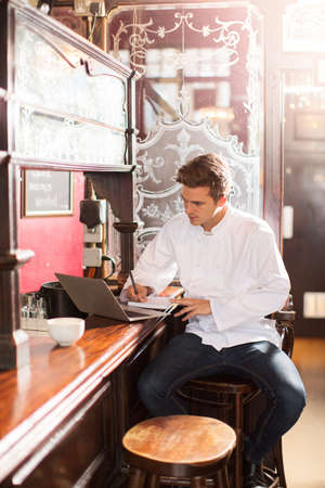 Young chef sitting on bar stool at work using laptop
