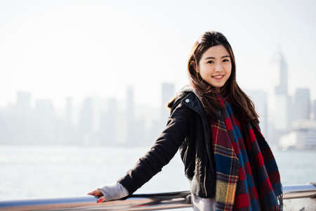 Portrait of young woman wearing checked scarf and leather jacket, looking at camera LANG_EVOIMAGES