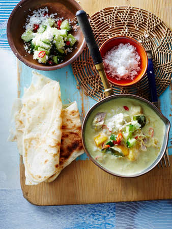 Overhead view of tuna curry in saucepan with flatbreads and salad LANG_EVOIMAGES