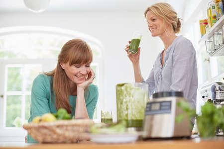 Women drinking green vegan smoothie in kitchen