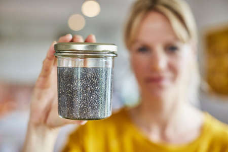 one mature woman only: Mature woman holding up jar of seeds, focus on seeds LANG_EVOIMAGES
