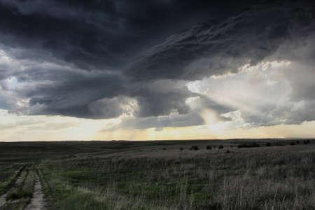 environmental issues: Dazzling crepuscular rays, anticyclonic split, cyclonic updraft, mesocyclone In background, Sidney, Nebraska, USA