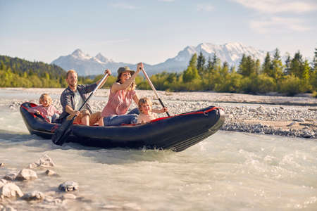 in unison: Family using paddles to steer dinghy on water, Wallgau, Bavaria, germany