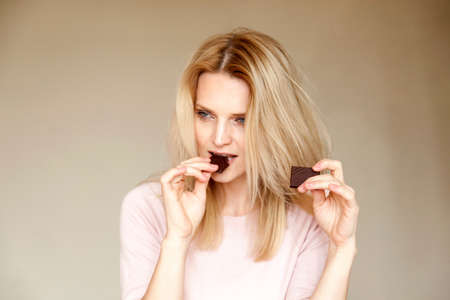 unfit: Portrait of beautiful woman with long blond hair eating chocolate bar LANG_EVOIMAGES