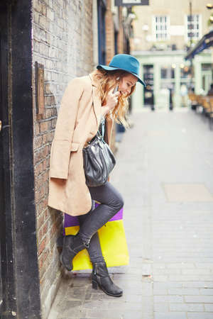 sleek: Stylish young female shopper chatting on smartphone, London, UK LANG_EVOIMAGES