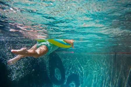 Underwater shot of girl kicking legs in swimming pool learning to swim with rubber ring