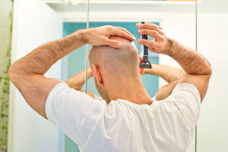 Rear view of young bald man shaving head in bathroom LANG_EVOIMAGES