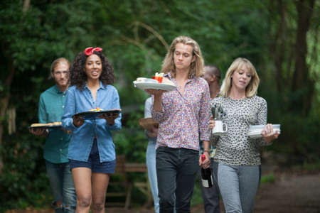 Friends carrying dishes to evening outdoor meal