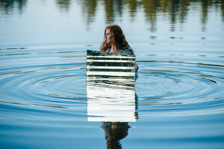 Young woman standing in lake, holding mirror, water ripples reflecting in mirror LANG_EVOIMAGES