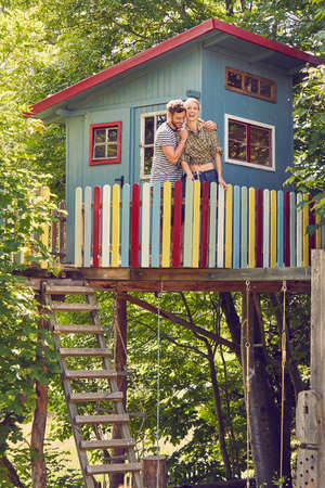 Young couple standing in tree house, hugging, laughing LANG_EVOIMAGES
